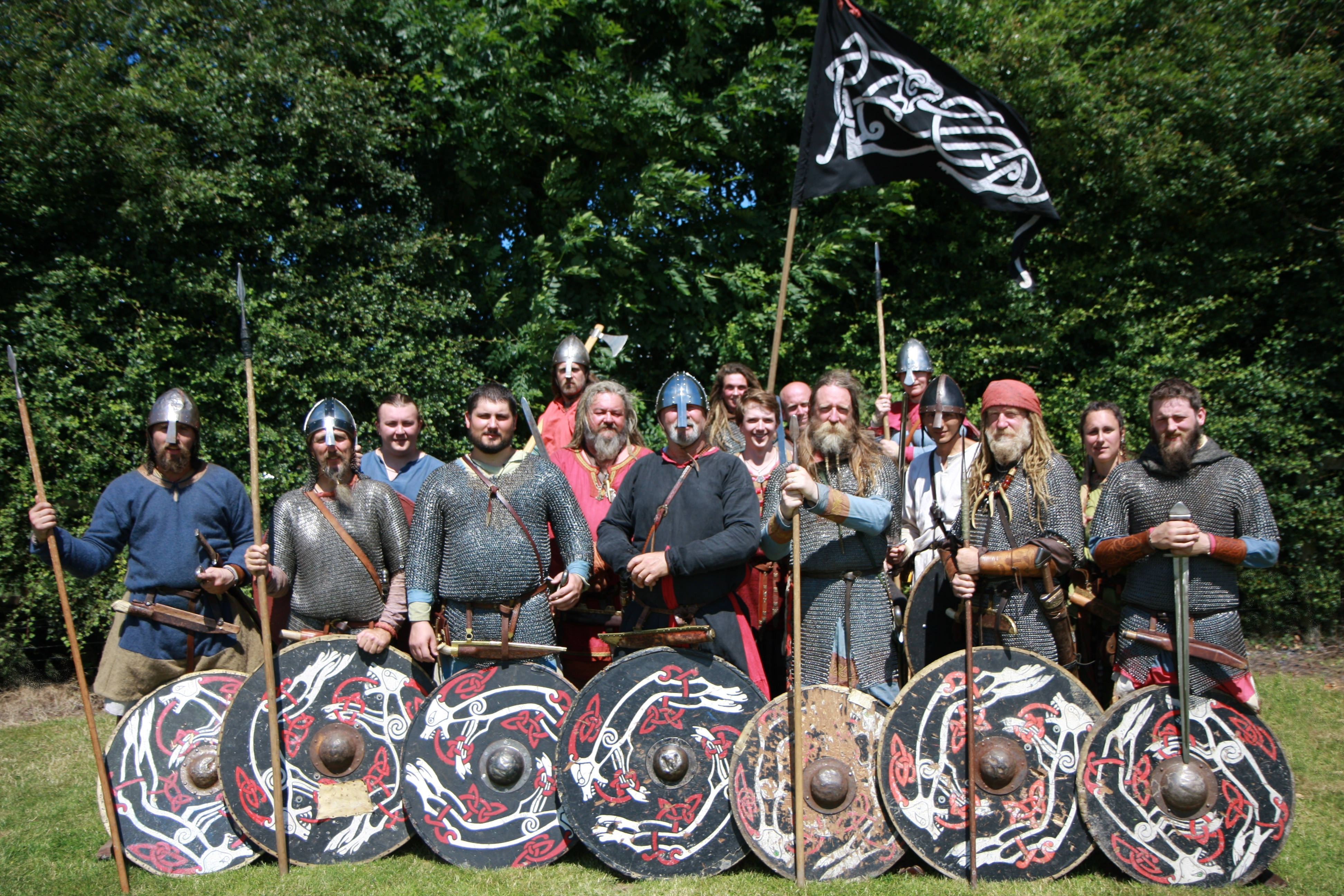 Group of warriors, with matching Black Dog shields and banner