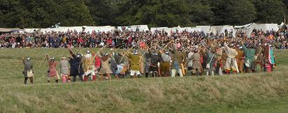 A large unit of archers drawing arrows, with crowd and tents in the distance