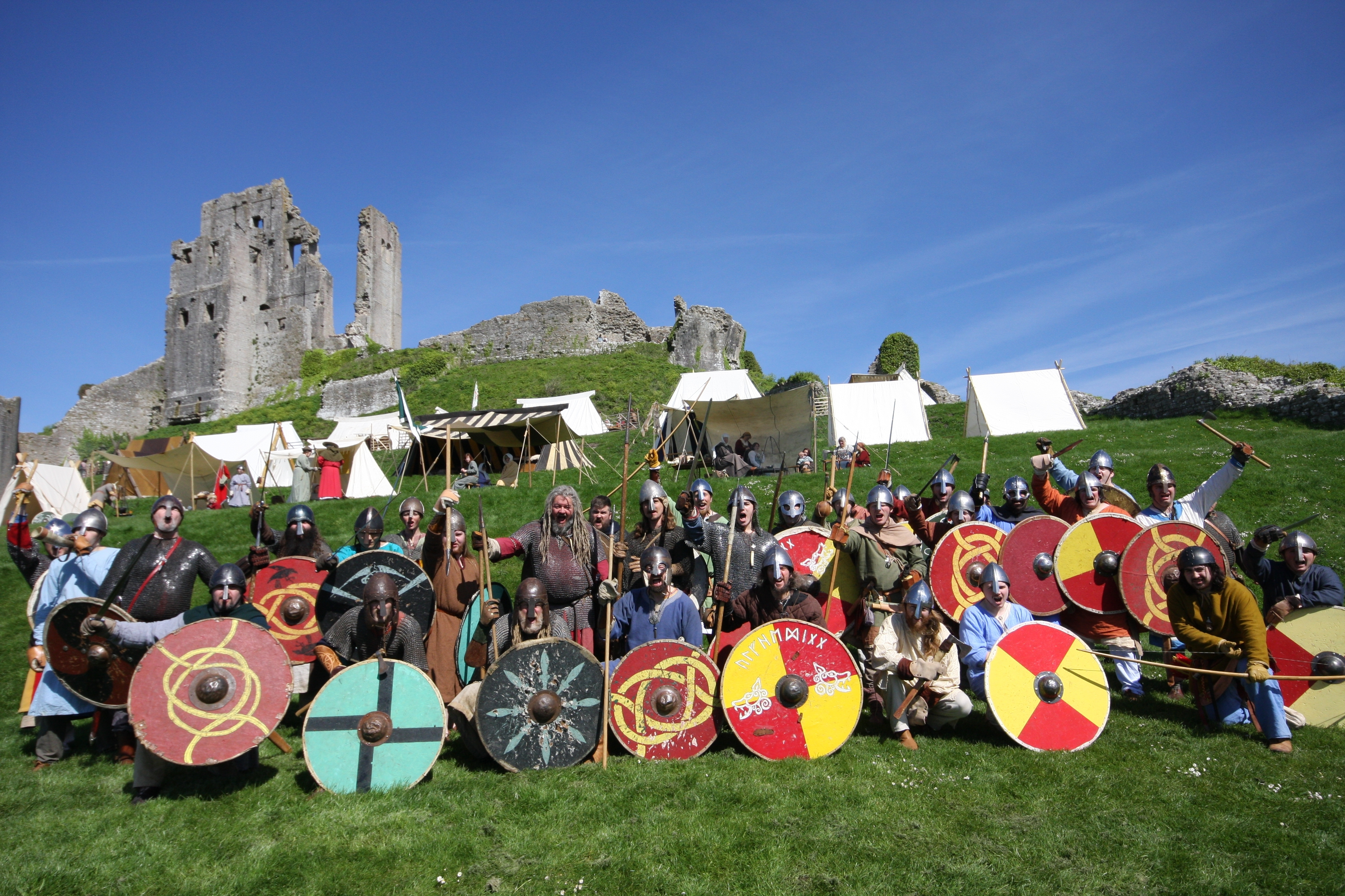 Cheering Vikings, in front of tents, Corfe Castle, and a brilliant blue sky