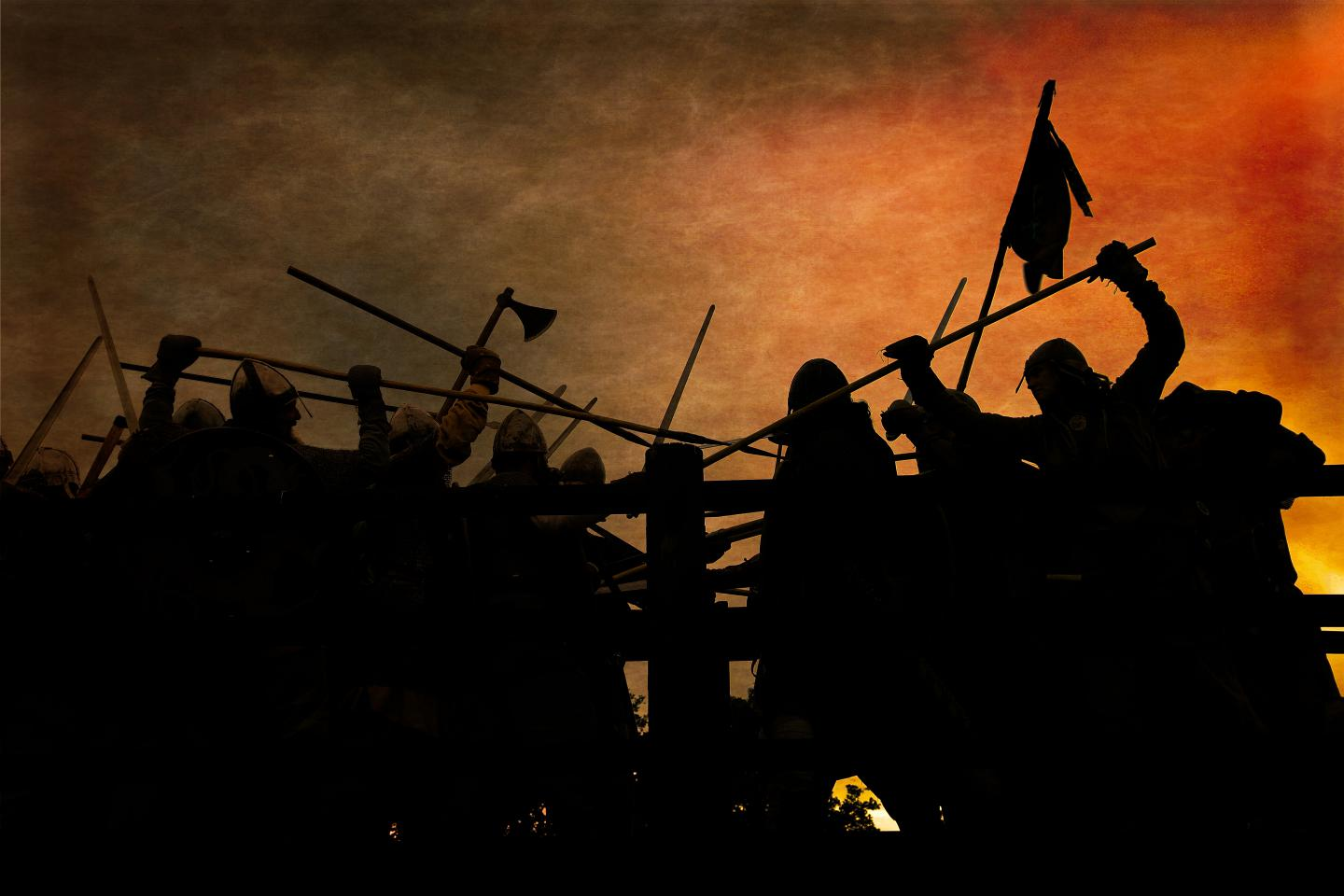 Warriors fighting, silhouetted against orange clouds