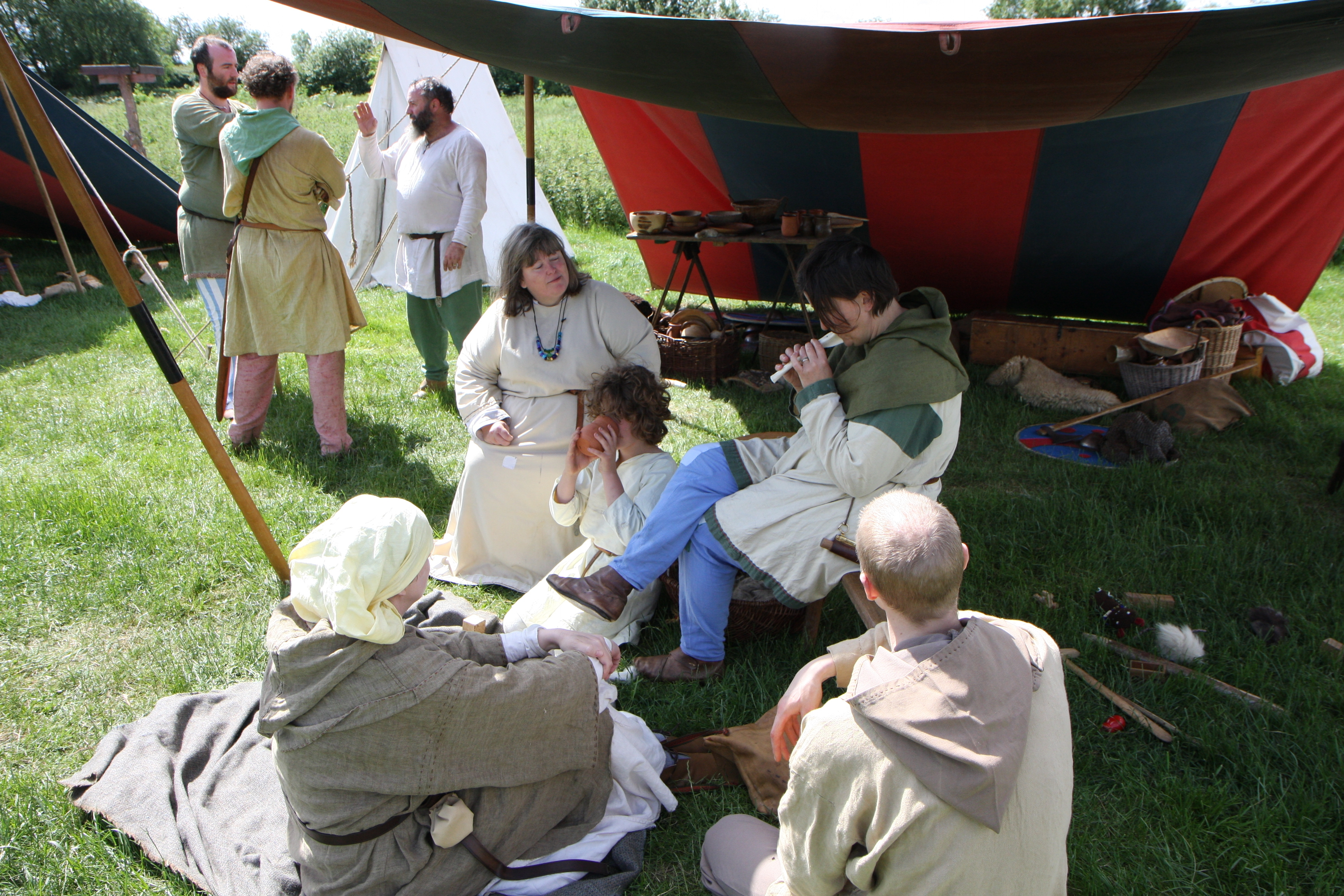 Vikings sitting under an awning; one plays a whistle