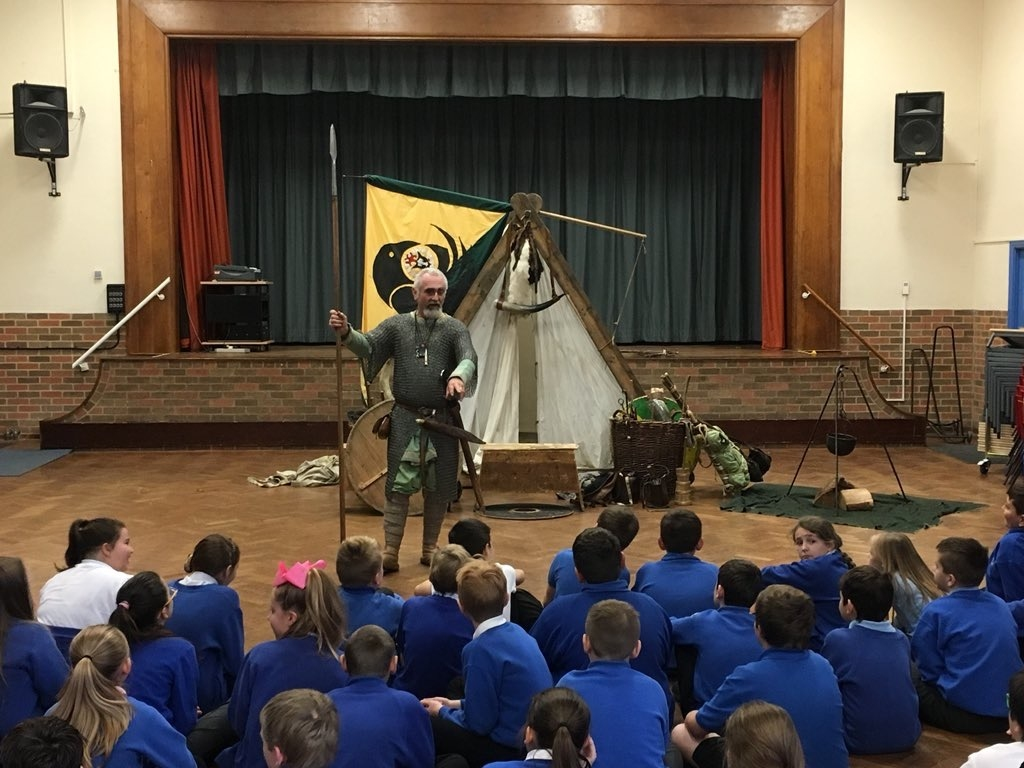 Viking with tent and cauldron, with children in school hall