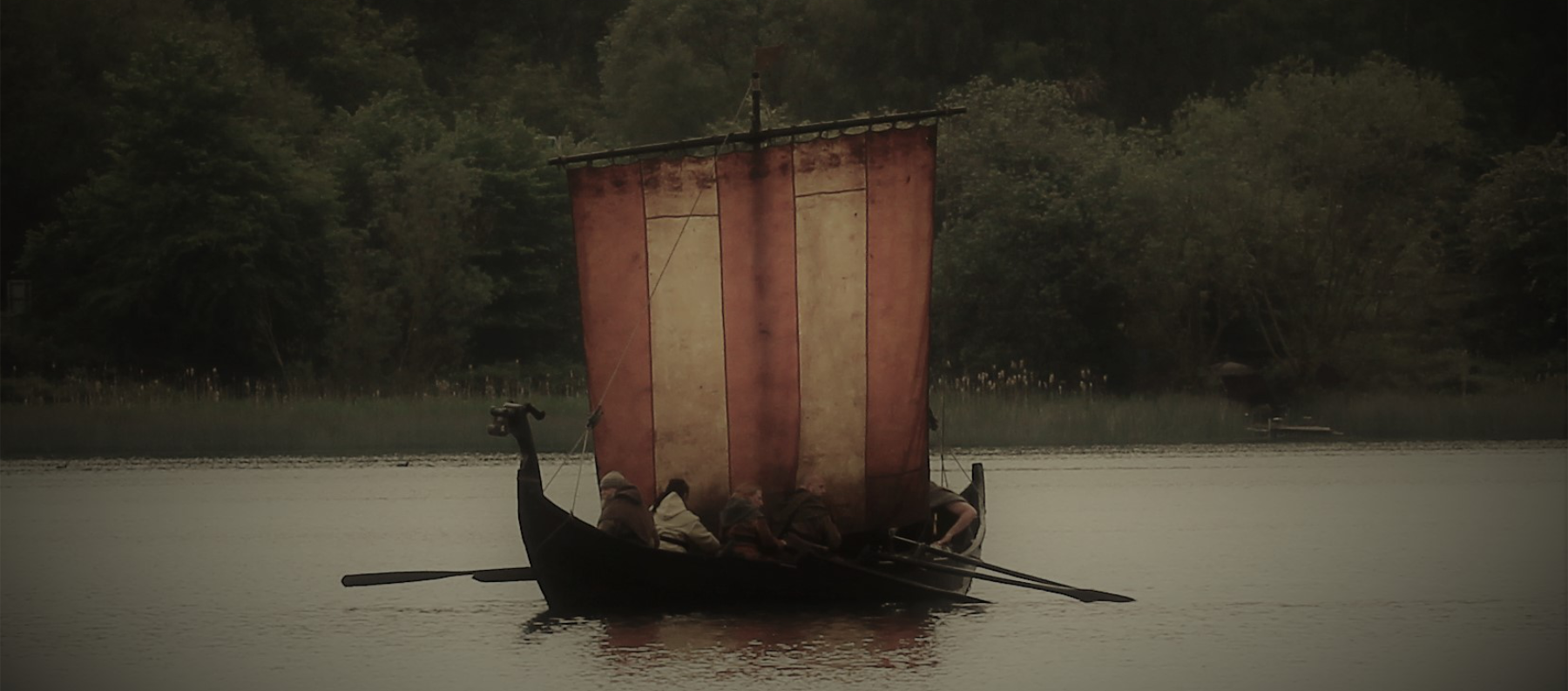 A small Viking boat, propelled by sail and oar