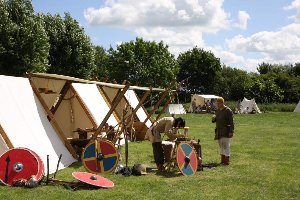 Vikings in a tented village with trees behind